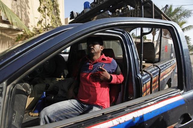 Asif Hassan, 1 nhiếp ảnh gia của hãng AFP, bị những người biểu tình bắn trúng ngực và đang phải ngồi trong xe cảnh sát tại Karachi, Pakistan ngày 16/1/2015.
