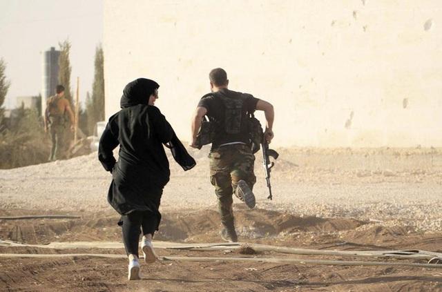 Một nữ phóng viên đang chạy trốn cùng một chiến binh nổi dậy để tránh các tay súng bắn tỉa trên chiến trường chống lại IS ở vùng nông thôn tỉnh Aleppo vào ngày 10/10/2014.