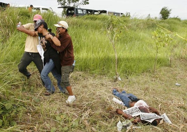 Cuộc tàn sát của 1 phe phái chính trị ở khu vực ngoại ô Ampatuan, Maguindanao, Philippines đã khiến một phóng viên tử nạn vào ngày 24/11/2009. Trong ảnh, người vợ của anh gần như ngã quỵ.