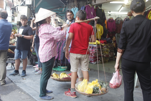 Người bán hàng rong đang chèo kéo khách tại phố Hàng Đường.