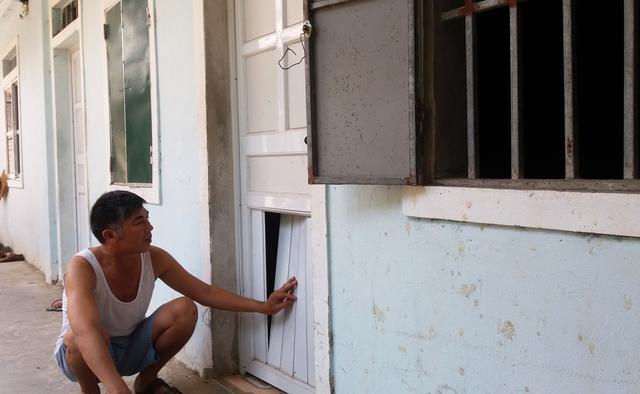 Ông Thuận kiểm tra và sửa chữa lại những cánh cửa phòng trọ bị hư hỏng do lâu ngày không có người ở.