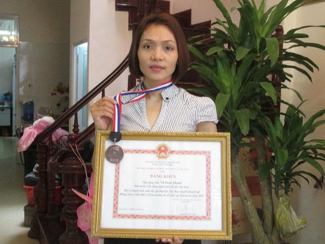 Chị Vũ Hoài Thanh bên cạnh giấy khen về thành tích trong hoạt động thể thao. Ảnh: Ngọc Thi