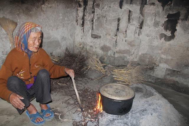Cụ Dung bên bếp lửa héo mòn ở cái tuổi 90. Ảnh: HH