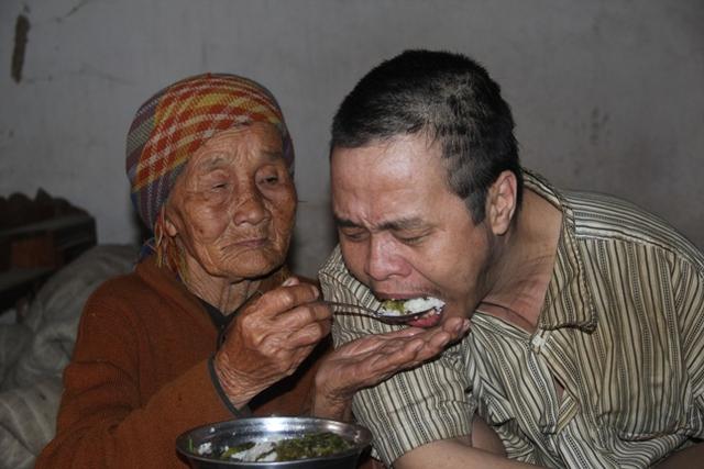 Cụ Dung chăm lo từng bữa cơm cẩn thận cho con trai mình. Ảnh: HH