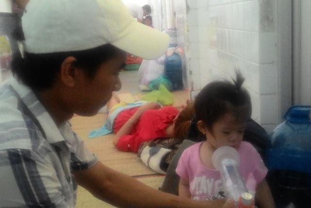 Anh Nguyễn Hữu Lực đang chăm con gái 16 tháng tuổi tại Khoa Hô hấp (Bệnh viện Nhi Đồng 1). Ảnh: Đỗ Bá