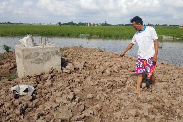 Anh Vũ Đức Thuận chỉ vị trí công nhân đổ bê tông lẫn đất khi làm móng cột điện. Ảnh: Cao Tuân