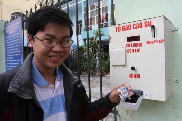 Trưởng nhóm Nguyễn Công Tín bên máy phát bao cao su miễn phí tự động đặt tại 180 Hoàng Diệu, Đà Nẵng. Ảnh: Đ.Hoàng