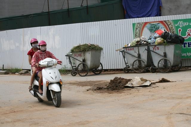 Rất nhiều điểm tập kết rác không phủ bạt, che chắn các xe thu gom.