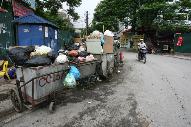 Hàng loạt xe thu gom rác không được che bạt nằm ngay đầu ngã ba phố Hoàng Ngân – Lê Văn Lương.