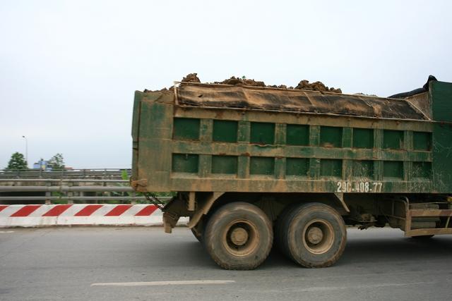 Theo quy định, các xe tải chở nguyên vật liệu dễ rơi vãi không được vượt quá thành xe.
