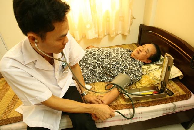 Điều dưỡng viên đo huyết áp cho thương binh Đoàn Minh Đức (71 tuổi).