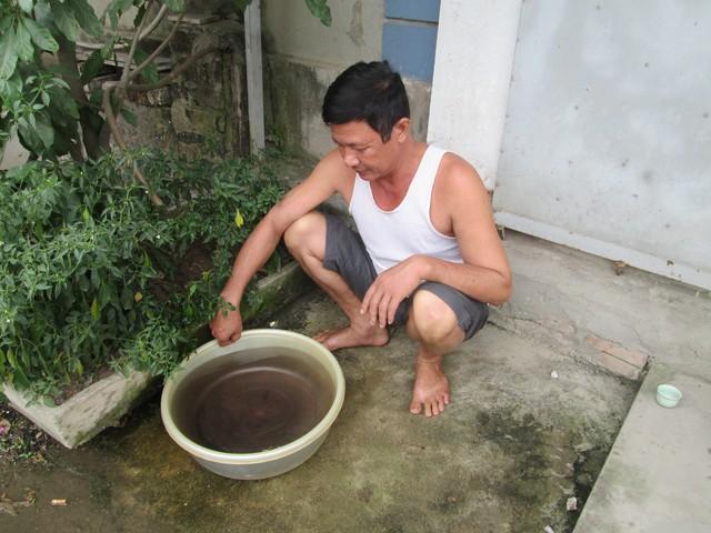 Ông Nguyễn Xuân Quang đổ chén trà nguội vào chậu nước, ngay lập tức nước chuyển màu đen. Ảnh: N.T