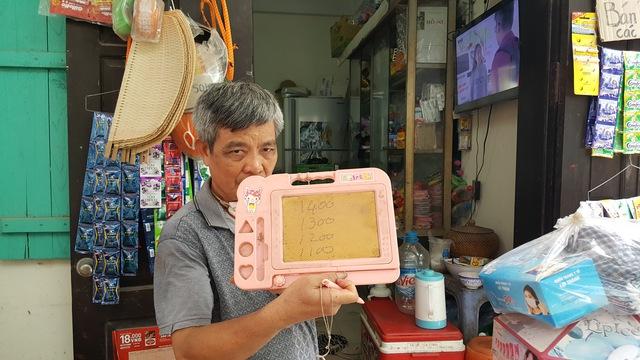 Ông Triệu Khắc Hòa với tấm bảng giá phòng trọ mà HTX Triều Khúc cho thuê.