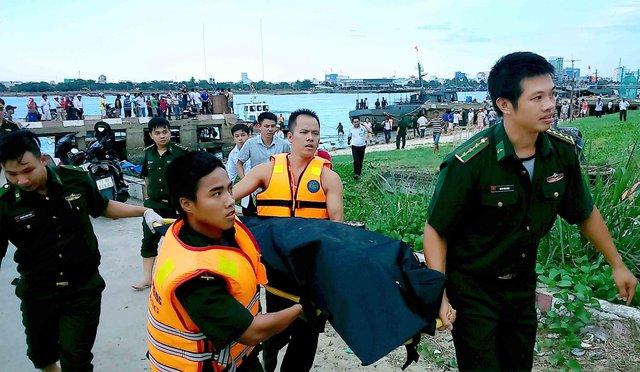 Lực lượng chức năng đưa thi thể tìm thấy lên bờ bàn giao cho gia đình. Ảnh: Quang Trung