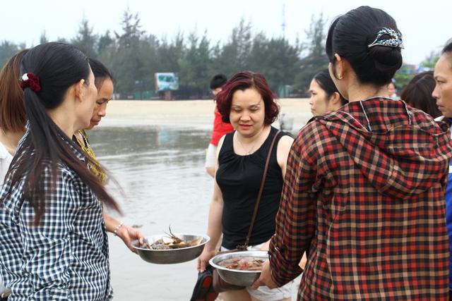 Một vị khách Hà Nội đang chọn mua hải sản ở bãi biển Cửa Lò.