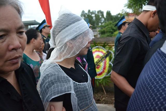 Chị Đỗ Thị Thuỳ Nga (vợ anh Lam) lầm lũi đi sau di ảnh của chồng. Ảnh: Đ.Tuỳ