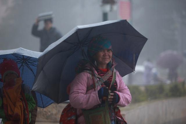Đêt chống chọi lại cái rét và mưa kéo dài, những người bán hàng đã quấn nhiều lớp áo ấm vào người và dùng ô che mưa.