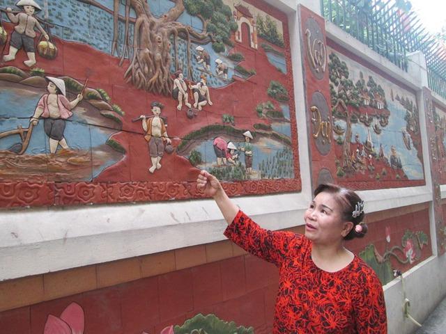 Bà Vũ Thị Bắc giới thiệu những họa tiết trên bức tranh. Ảnh: Ngọc Thi