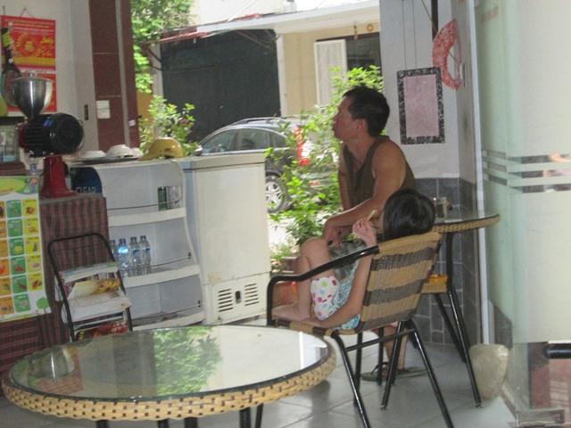 Hằng ngày, anh Ánh trông quán, vắng khách thì cùng con gái xem truyền hình. Ảnh: Ngọc Thi