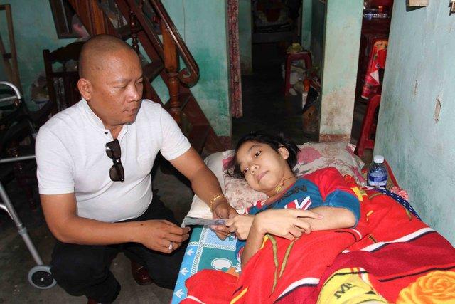 Anh Phạm Trường Tuấn trao tiền hỗ trợ cho em Nhung trong một lần về quê. Ảnh: Đức Hoàng