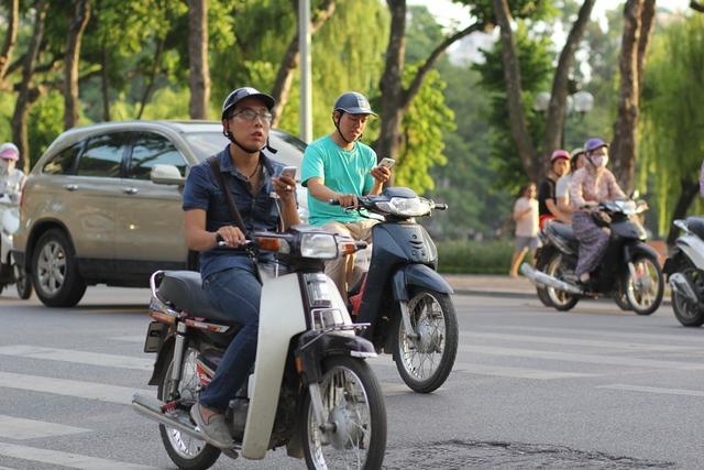 Tuy nhiên, điều đáng lo ngại là không ít người đang điều khiển xe máy giữa phố đông đúc nhưng vẫn cầm smartphone và dán mắt vào màn hình.