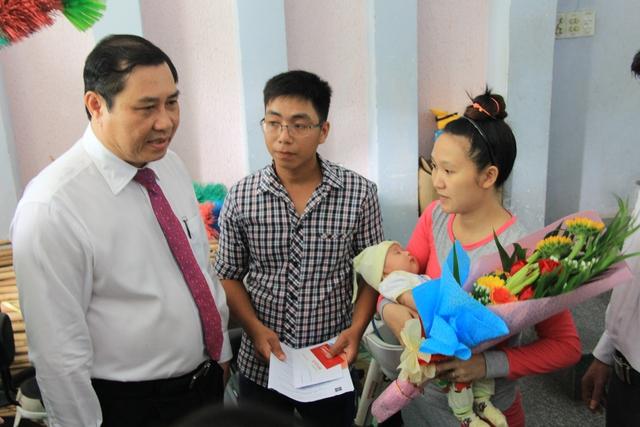 Chủ tịch UBND TP Đà Nẵng Huỳnh Đức Thơ tặng hoa và trao hồ sơ 3 trong 1 cùng sổ tiết kiệm 1 triệu đồng cho gia đình vợ chồng anh Nguyễn Thanh Phong (trú phường Mân Thái, quận Sơn Trà) chiều 3/10. Ảnh: Đức Hoàng