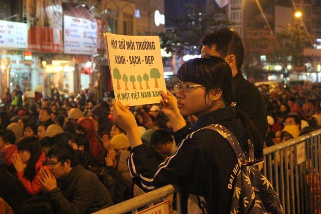 Sinh viên trường Đại học Ngoại ngữ phối hợp với nhà chùa tuyên truyền người dân không vứt rác sau khi làm lễ.