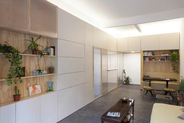 Công ty thiết kế đưa ra giải pháp thay thế bức tường ngăn cách giữa phòng khách với bếp bằng một hệ tủ đồ.