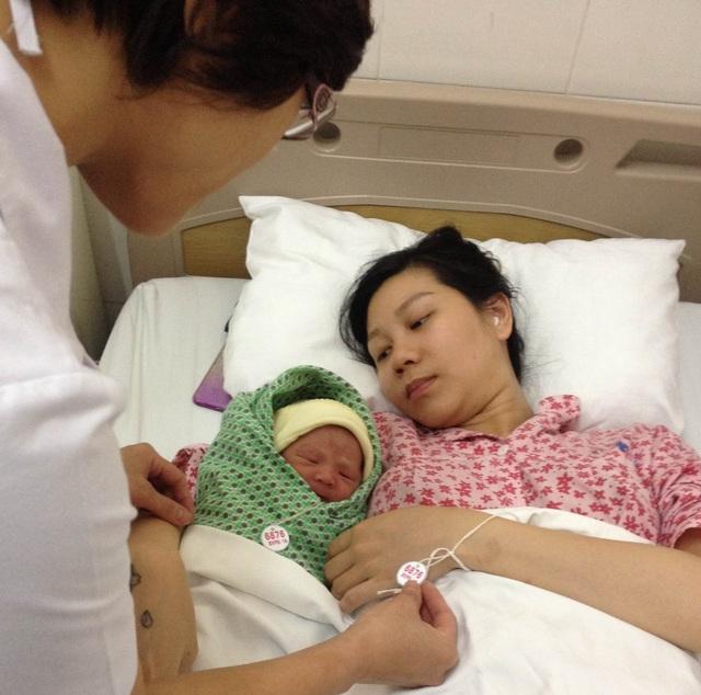 Nhân viên y tế kiểm tra số trên bộ vòng 2 mẹ con sản phụ. Ảnh: Võ Thu