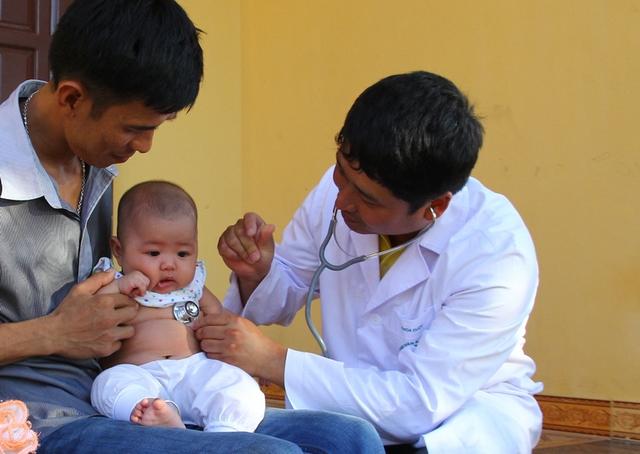 Bác sĩ Nguyễn Thành Nam - Trưởng Khoa nhi - Bệnh viện Bạch Mai đang thăm khám sức khỏe cho bé Thùy tại nhà của bé.