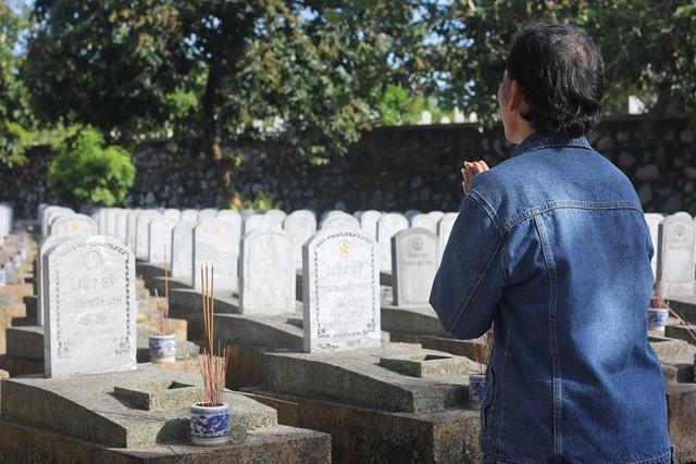 Ông Nguyễn Văn Hoàn dâng hương trước trùng điệp ngôi mộ chưa biết tên. Ảnh: Nguyễn Hồng Quân