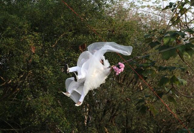 Một đôi vợ chồng Thái Lan bay bằng cáp trong khi đang thực hiện lễ thành hôn. Đám cưới của họ tổ chức ngay trước ngày Valentine tại Prachin Buri, một tỉnh ở phía đông Bangkok.
