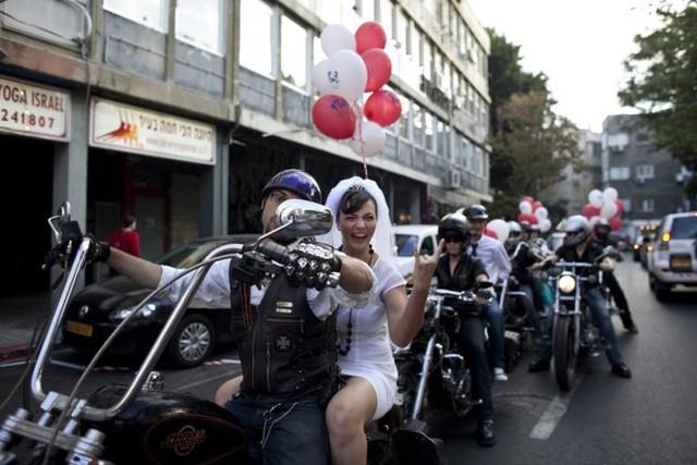 Cô dâu Yulia Tagil đang ngồi sau một chiếc xe máy phân khối lớn để đến nơi diễn ra cưới của mình ở Tel Aviv, Israel.