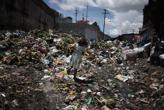 Khi rác ngày càng chất cao dần, việc di chuyển hay đi lại từ nơi này sang nơi khác càng trở nên khó khăn, đặc biệt đối với lũ trẻ. Trong ảnh, một bé gái đang bước qua biển rác ở chợ thực phẩm La Terminal, ở thành phố Guatemala, Cộng hòa Guatemala.