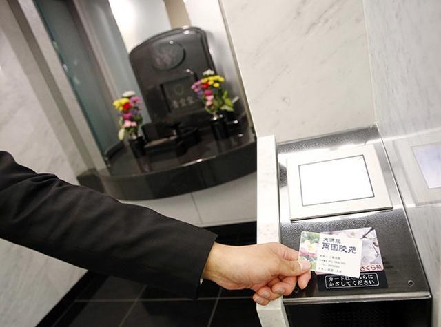 Việc đầu tư kinh doanh tang lễ tăng lên kéo theo nhiều công nghệ tiên tiến và sáng tạo, mang thương hiệu Nhật Bản. Ryogoku Ryoen, nghĩa địa nhiều tầng ở Tokyo, được lắp đặt một hệ thống tìm bia mộ hoặc bình đựng tro cốt chính xác dựa vào một loại thẻ nhận dạng được cung cấp.Trong ảnh, một nhân viên đang hướng dẫn cách sử dụng ngôi mộ hiện đại bằng tấm thẻ nhận dạng danh tính tại nghĩa trang Ryogoku Ryoen.