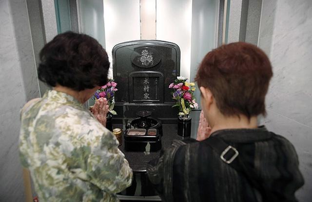 """Bà Yukiko Kimura (phải) tới thăm người chồng đã khuất cùng chị chồng. """"Nhà mới"""" của chồng bà Yukiko là một ngôi mộ hiện đại đặt tại nghĩa trang Ryogoku Ryoen."""