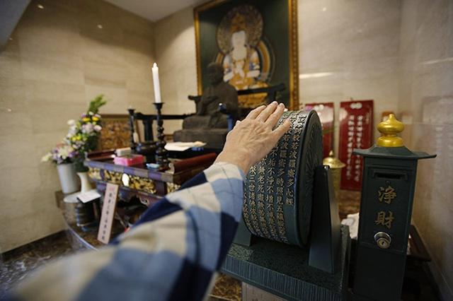 Một vị khách quay bánh xe cầu nguyện đặt trước một bức tượng Phật tại nghĩa trang Ryogoku Ryoen.
