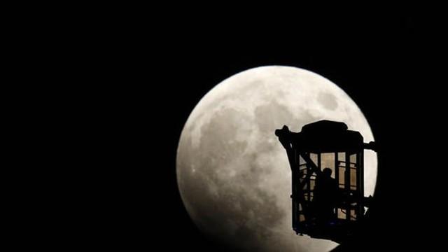 Một người đàn ông và một phụ nữ ngắm trăng khi nguyệt thực toàn phần bắt đầu vào tối 8/10. Ảnh: Reuters