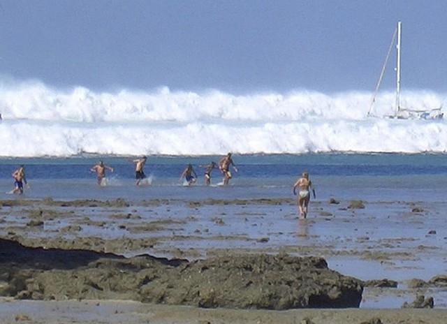 Ảnh chụp ngày 26/12/2004. Khi đó, những du khách nước ngoài đang bơi tại bãi biển Hat Rai Lay, gần Krabi, ở miền nam Thái Lan hốt hoảng chạy vào bờ khi trông thấy những ngọn sóng cao cuồn cuộn. Ảnh: AFP