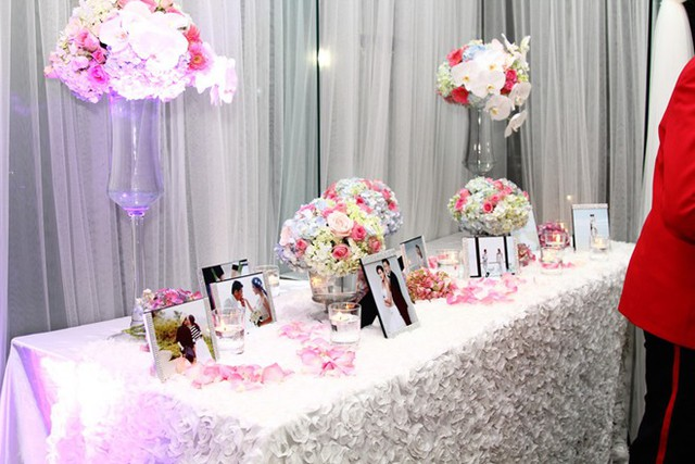 Tại khu vực sảnh của nhà hàng, anh dùng một bàn dài để trưng hoa và những tấm ảnh cưới lẫn đời thường của cặp đôi. Bộ ảnh cưới lãng mạn của