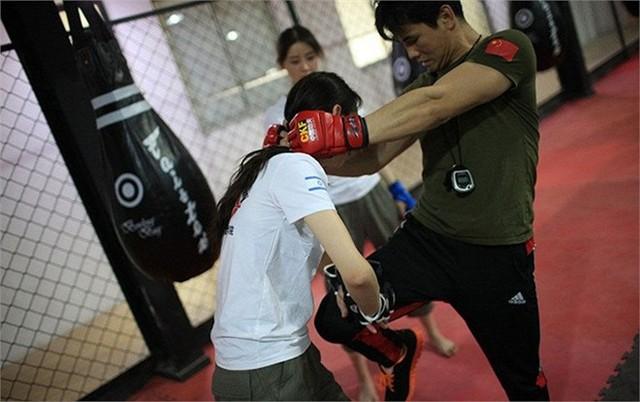 Nữ học viên dùng hai tay phản lại đòn tấn công từ huấn luyện viên.