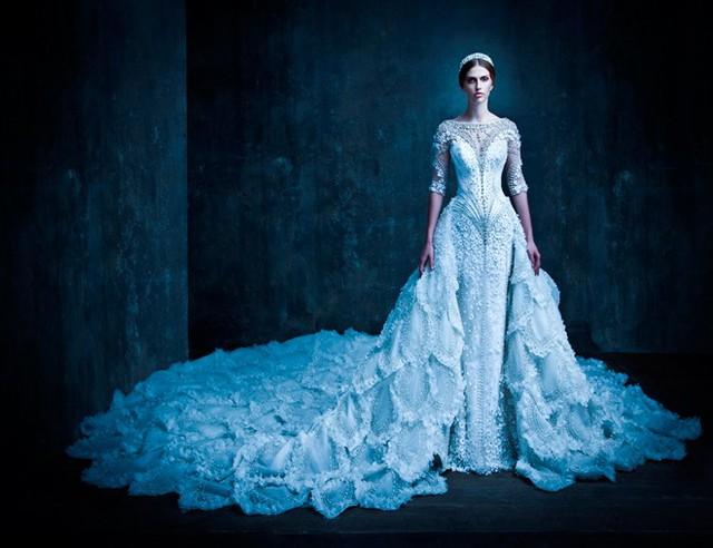 Những thiết kế mới nhất của Micheal Cinco trong bộ sưu tập váy cưới thu đông 2015 luôn hướng đến vẻ đẹp kiêu sa từ các hoa văn 3D trắng ngần kết tinh tế trên nền vải tiệp màu.