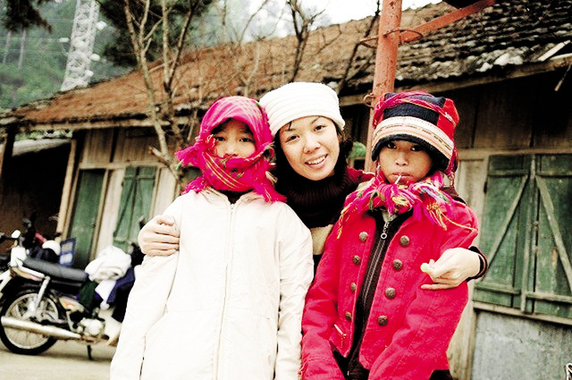 Tác giả với một trong hai em bé vì không có tiền mà phải nghỉ học ở Yên Minh, Hà Giang. Ảnh: T. D