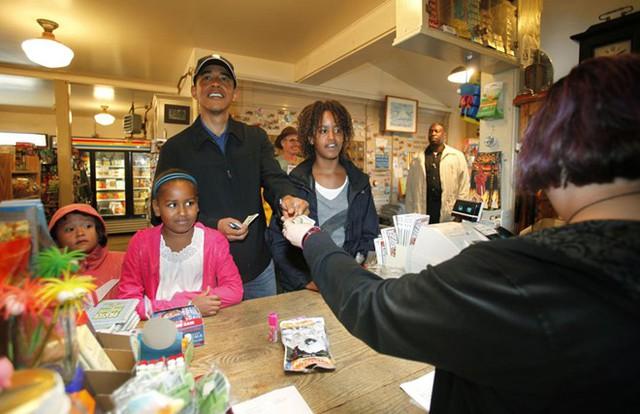Tổng thống Mỹ Barack Obama trả tiền cho bữa ăn nhẹ cho con gái của mình Sasha (2 L) và Malia (R) và cháu gái của ông Suhalia Ng (L) tại General Store Alley ở Tây Tisbury, Vineyard của Martha, August 30, 2009 trong ngày cuối cùng của kỳ nghỉ của mình . (Jason Reed / REUTERS)