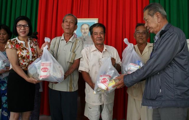 Lương y Nguyễn Văn Dậu (phải) và bà Huỳnh Thị Thu Sang, đại diện đơn vị phân phối sản phẩm gia dung Bosch tại TPHCM, trao quà đến bà con nghèo xã Phú Lộc.