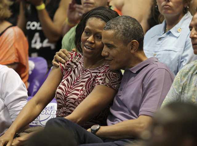 U.S President Barack Obama hugs first lady Michelle as they watch the Diamond Head basketball game between Oregon State and Akron during their Christmas vacation in Honolulu, Hawaii, December 22, 2013. (Hugh Gentry/REUTERS)