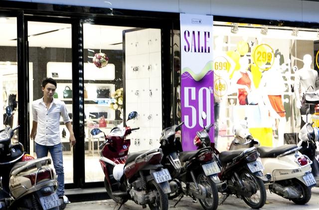 Các cửa hàng luôn treo biển giảm giá nhưng vẫn không hút được khách.Ảnh: Chí Cường
