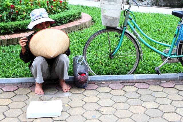 Bà Đặng Thị Lại làm nghề cân sức khỏe cho người tập thể dục buổi sáng tại hồ Thuyền Quang.