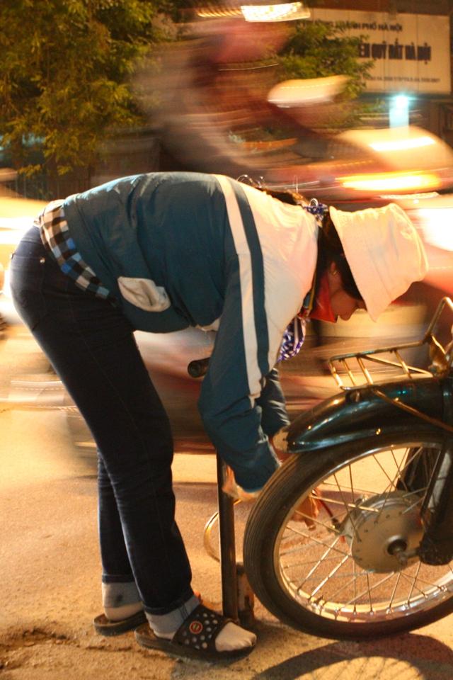 Một người phụ nữ làm nghề bơm vá xe buổi đêm trên đường Lê Văn Lương.