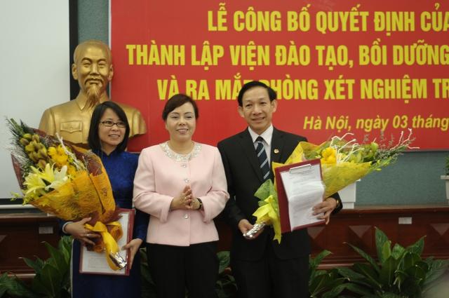 Bộ trưởng Bộ Y tế (giữa) tặng hoa PGS.TS Bùi Thu Hà, Hiệu trưởng Trường ĐHYTCC và PGS.TS Phan Văn Tường, Viện trưởng Viện Đào tạo, bồi dưỡng cán bộ quản lý ngành y tế.